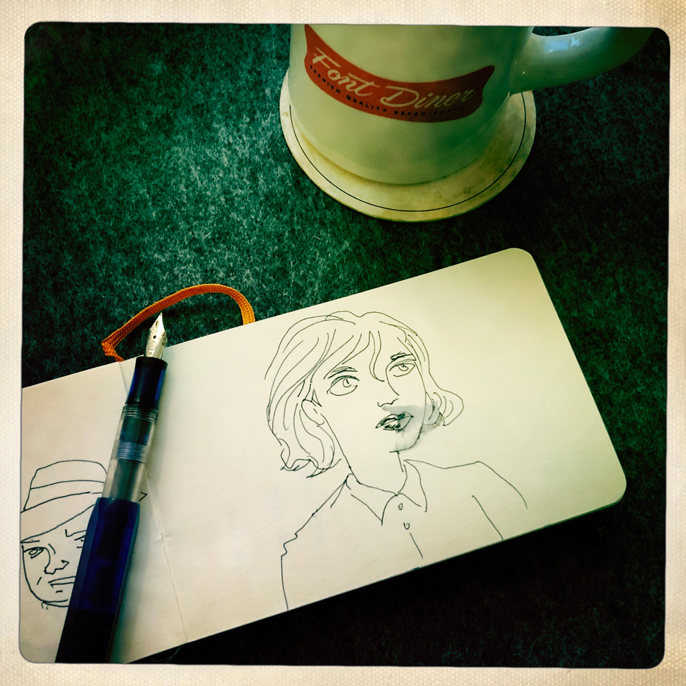 Photo of a coffee cup and a sketchbook. The drawing is of a woman.