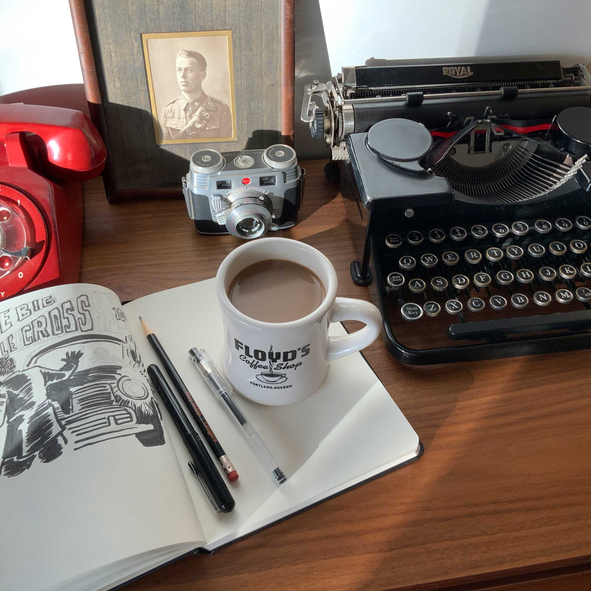 Photo fo sketchbook, a coffee cup, old camera and an old Royal typewriter.