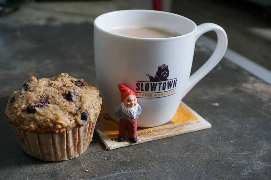 Photo of a coffee cup, a muffin, and a gnome.