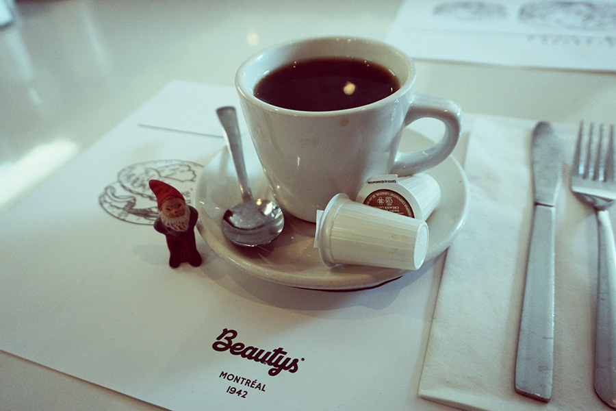 photo of diner coffee and a small garden gnome. Montreal, Quebec, Canada