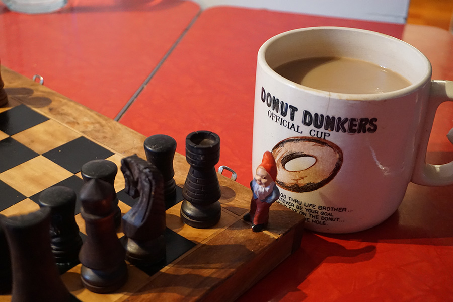 photo of a garden gnome on a chess set with a coffee cup. British Columbia, Canada